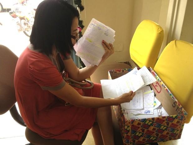 A professora Siane Guimarães adotou sete cartas e diz contribuir com o projeto há anos. (Foto: Vanessa Vasconcelos/G1)