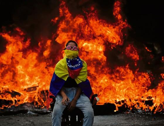 Em Caracas  manifestantes em frente a barricada em chamas  (Foto: Ronaldo SCHEMIDT/AFP)