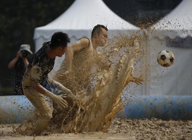 Chineses participam de um campeonato de futebol disputado na lama. Realizado na capital Pequim, o torneio reúne 32 equipes locais. (Foto: Kim Kyung-Hoon/Reuters)