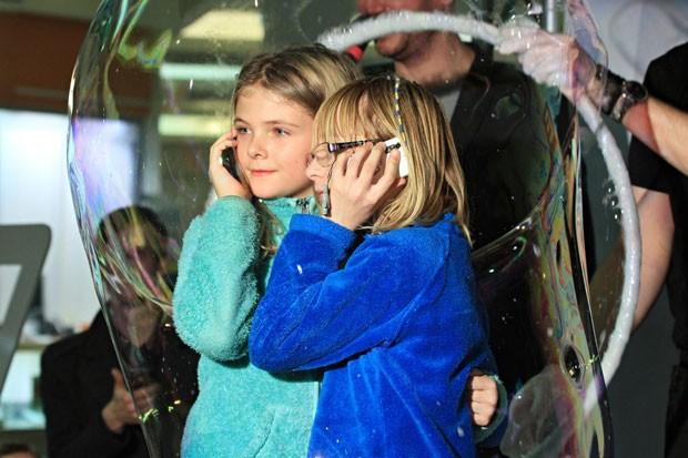 Meninas falam ao celular enquanto são engolidas por bolha gigante de sabão (Foto: Radek Mica/AFP)