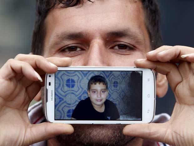 Said, de Terã, no Irã, mostra a foto do filho Hossein ao esperar na fronteira (Foto: REUTERS/Srdjan Zivulovic)