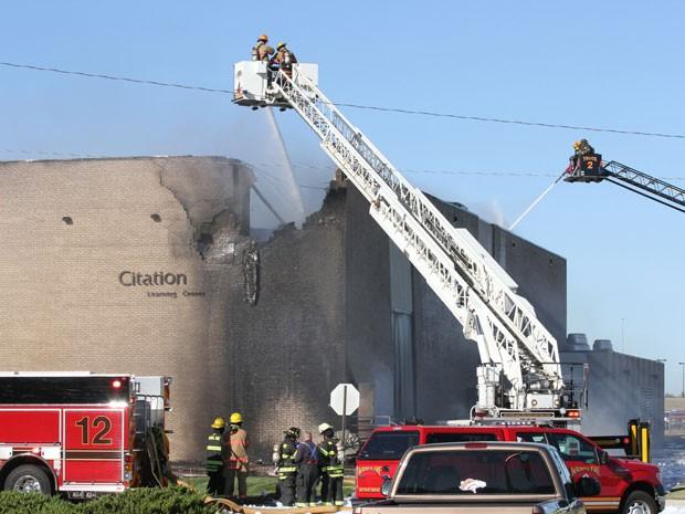 Bombeiros tentam conter incêndio em prédio do aeroporto de Mid-Continent, em Wichita, após colisão de avião de pequeno porte (Foto: AP Photo/The Wichita Eagle, Brian Corn))