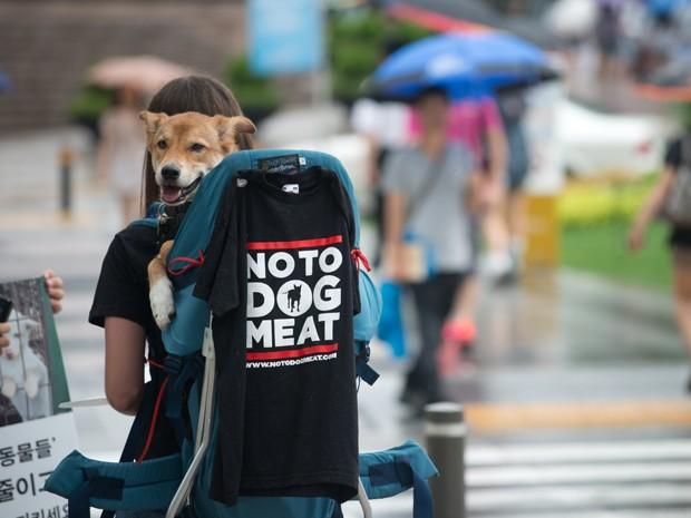 Manifestante carrega um cão e exibe uma camiseta condenando o consumo de carne de cachorro na Coréia do Sul, durante um protesto de grupo de defesa dos animais, em Seul, neste sábado (13). A carne de cachorro é usada na preparação de pratos na Coreia do Sul (Foto: Reuters)