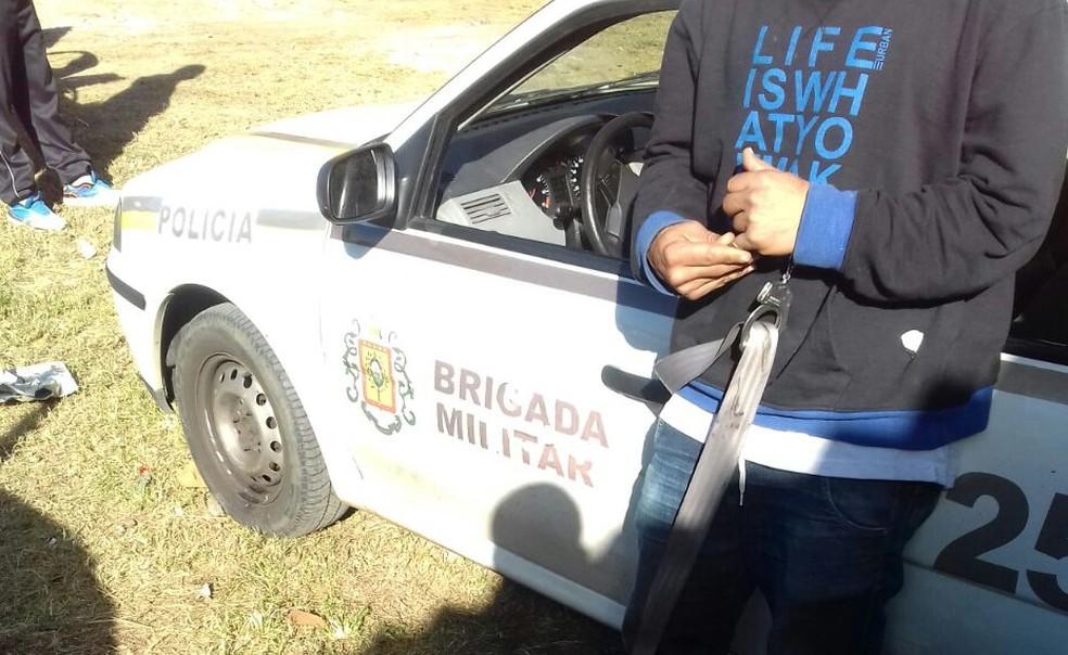 Preso é algemado ao cinto de segurança da viatura (Foto: Brigada Militar/Divulgação)