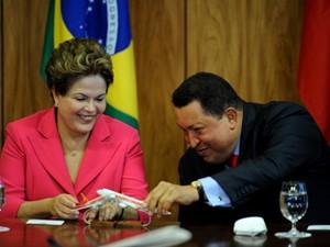 Dilma Rousseff e Hugo Chávez brincam com aviões em miniatura durante assinatura de acordo (Foto: PEDRO LADEIRA / AFP)