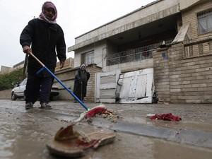 Morador limpa local de um dos ataques a bomba contra cristãos nesta sexta-feira (31) em Bagdá, capital do Iraque. (Foto: AP)