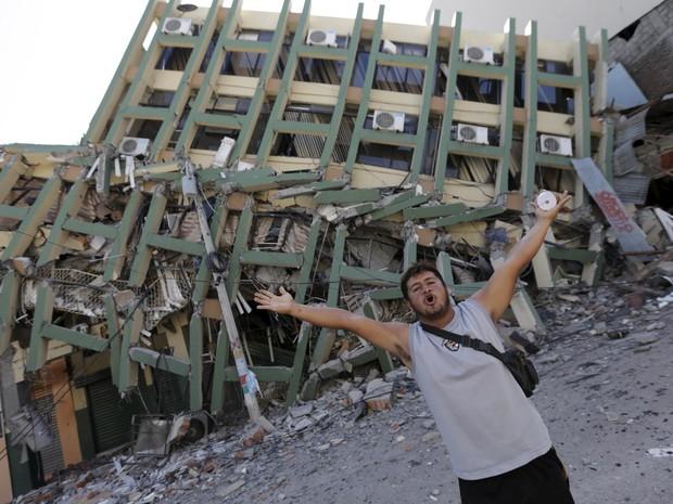 Um morador abre os braços em frente a um prédio desmoronado após um terremoto atingir a costa do Pacífico em Portoviejo, no Equador (Foto: Henry Romero/Reuters)