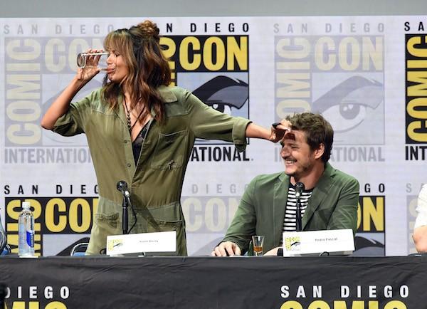 A atriz Halle Berry virando o copo de whisky enquanto é observada pelo ator Pedro Pascal (Foto: Getty Images)