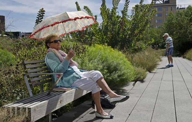 Uma senhora de sombrinha protege-se do sol forte do final de verão, descansando em um dos inúmeros bancos do High Line (Foto: © Haroldo Castro/Época)
