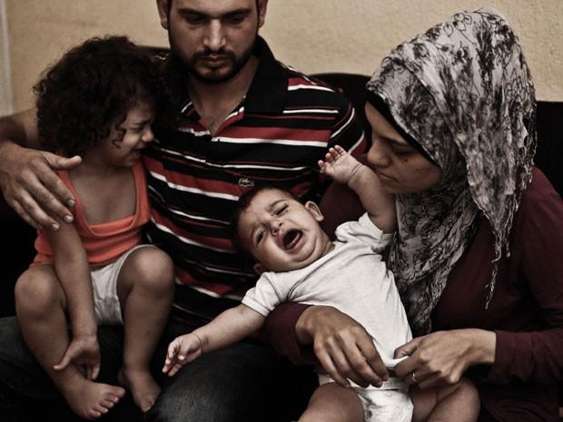 Abdallah e Nisreen Mohammed com os filhos no apartamento que dividem com outra família (Foto: Gabriel Chaim/G1)
