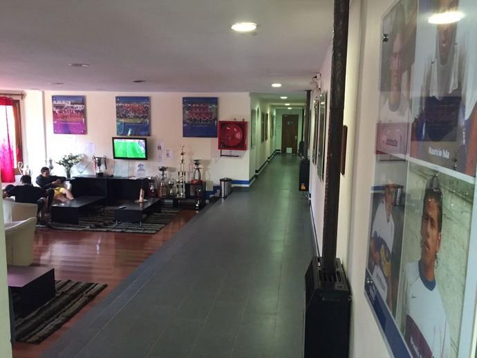 Alojamento para dezenas de jovens fica ao lado do estádio da Católica: na parede, um pouco da história do clube com ídolos em postêresA sala (Foto: Raphael Zarko)