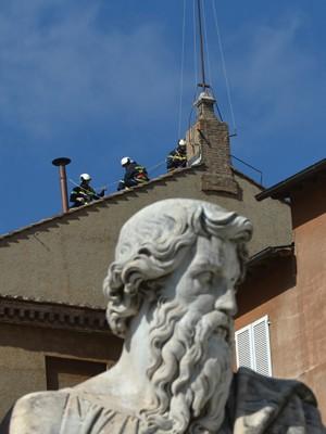 Bombeiros instalam chaminé no teto da Capela Sistina neste sábado (9) no Vaticano (Foto: Gabriel Bouys/AFP)