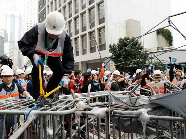 Funcionário usa um alicate de corte para desmantelar barricada em Hong Kong. (Foto: Tyrone Siu /Reuters)