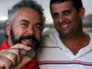 Os pesquisadores com a moeda encontrada em Cabo Frio. (Foto: Walmor Freitas)