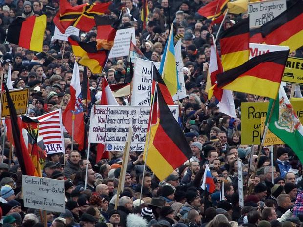 Pessoas levaram bandeiras da alemanha em protesto contra Islã organizado pelo movimento Pegida na Alemanha (Foto: AP Photo/Michael Sohn)
