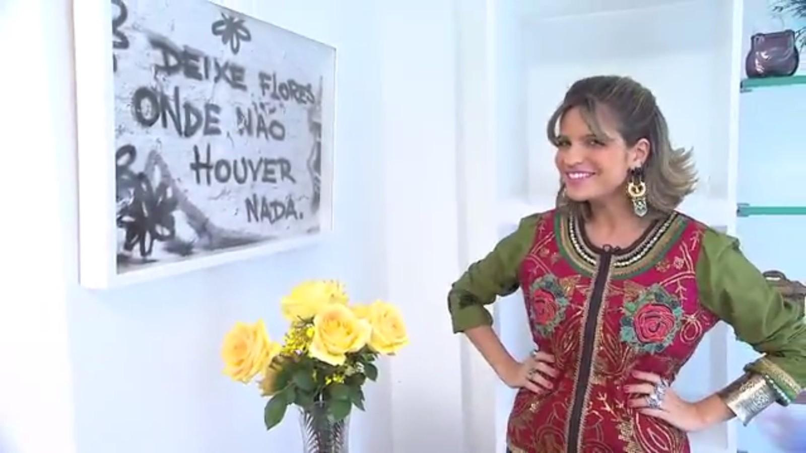 """Paula Magalhães posa ao lado do quadro """"Deixe flores onde não houver nada"""" (Foto: Divulgação)"""