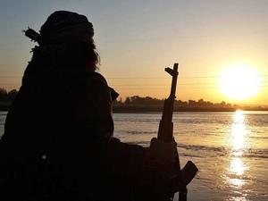Combatente do Estado Islâmico segura arma AK-47 ao relaxar na beira do rio Eufrates, em Raqqa (Foto: Militant website via AP)