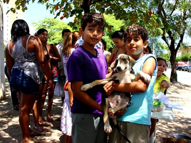 Irmãos Hyan Fernando e Huan Héricles exibem animal adotado.  (Foto: Jonathan Lins/G1)