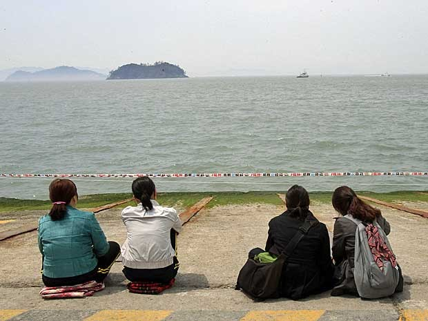 Parentes de passageiros desaparecidos após balsa virar e afundar na coreia do sul olham para enquanto esperam por informações do acidente. (Foto: Ahn Young-joon / AP Photo)