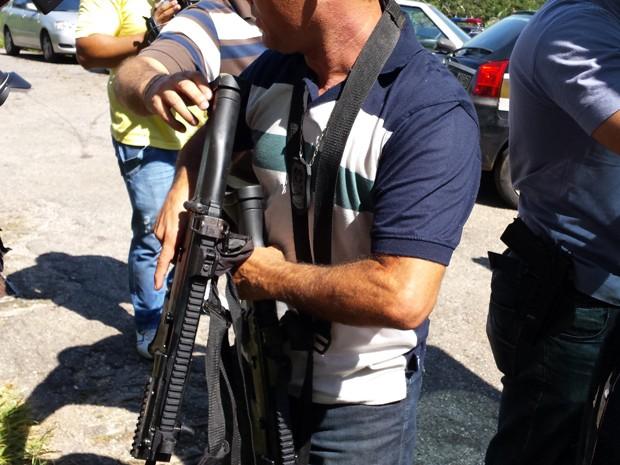 Policial exibe uma das armas roubadas da Central de Escoltas e que foi recuperada. (Foto: Raquel Freitas/ G1 MG)