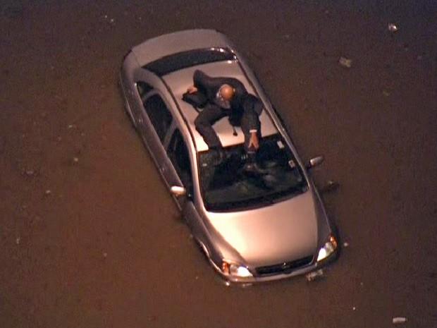 Motorista se refugia no teto do carro que ficou retido em alagamento em avenida de São Paulo (Foto: Reprodução/TV Globo)