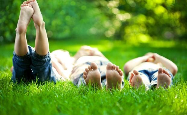 Crianças deitadas na grama com os pés para cima (Foto: Shutterstock)