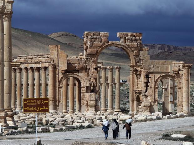 Em foto de 14 de março de 2014, sírios caminham pela antiga cidade de Palmira, a 215 quilômetros de Damasco (Foto: AFP Photo/Joseph Eid)