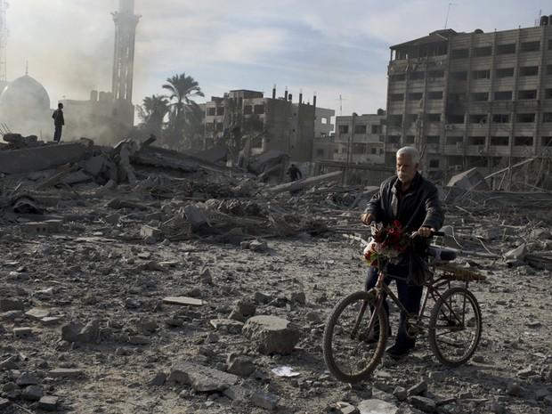 21 de novembro - Homem conduz sua bicicleta com flores perto de escombros de um prédio que foi destruído durante a noite na cidade de Gaza (Foto: Tyler Hicks/The New York Times)