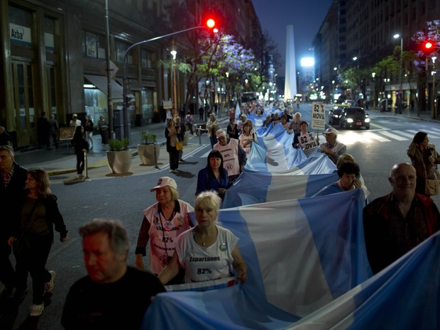 Manifestantes levam bandeira da Argentina durante caminhada em Buenos Aires (Foto: Natacha Pisarenko/AP)