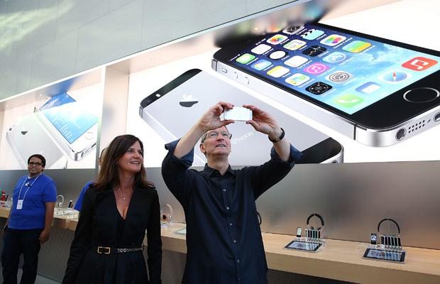 Tim Cook, presidente executivo da Apple, testa novo iPhone ao lado de Katie Cotton, uma das vice presidentes da empresa, no dia do início das vendas do iPhone 5S e do iPhone 5C. (Foto: Justin Sullivan/France Presse)