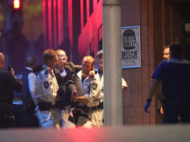 Uma refém ferida é carregada por paramédicos do lado de fora do Lind Cafe em Sydney, na Austrália (Foto: Rob Griffith/AP)