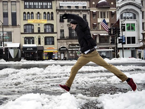 Homem pula poça em na avenida Connecticut, em Washington. O distrito de Washington teve a primeira forte tempestade de inverno nesta quinta-feira (13). (Foto: Brendan Smialowski/AFP)