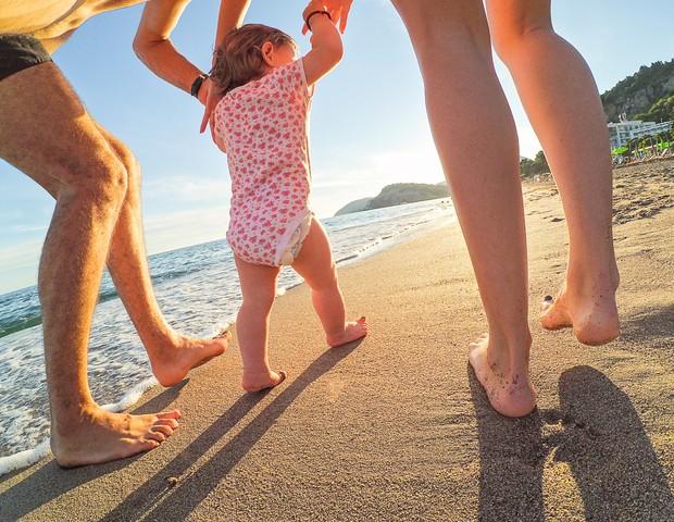 Criança de mãos dadas na praia (Foto: ThinkStock)