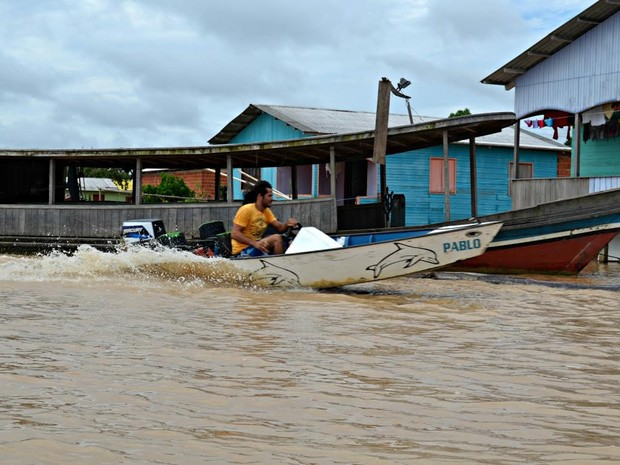 Moradores usam embarcações para chegar em casa (Foto: Tácita Muniz/G1)