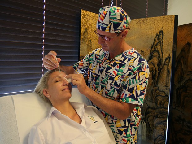 O cirurgião italiano Roberto Viel faz um tratamento na cliente, também italiana, Irina Tzoneva, em Dubai (Foto: Kamran Jebreili/AP)