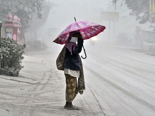 Mulher anda por uma estrada coberta por cinzas vulcânicas em Yogyakarta, na Indonesia, nesta sexta-feira (14). (Foto: Slamet Riyadi/AP)