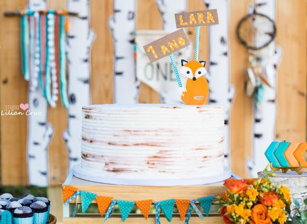 O bolo que tem o aspecto de casca de árvore, tem uma raposinha com o nome e a idade da aniversariante no topo e retalhos nas cores da festa na base (Foto: Divulgação / Lilian Cruz)