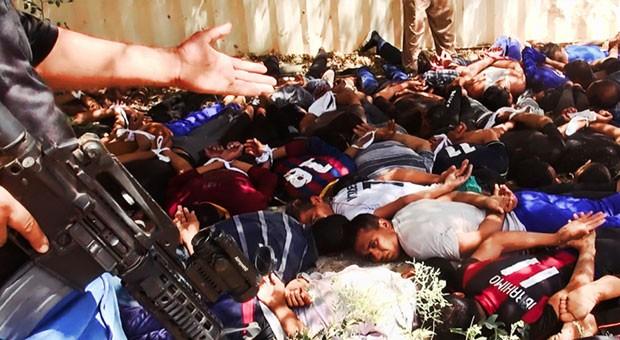 Imagem publicada em site militante no dia 14 de junho mostra integrantes do Estado Islâmico do Iraque e do Levante (EIIL) ameaçando soldados iraquianos capturados em Tikrit. Esta imagem e outras analisadas mostram que houve execuções em massa no país, seg (Foto: AP Photo via militant website)