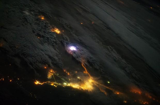 Foto tirada a partir da ISS mostra região entre Kwuait e Arábia Saudita: um relâmpago é visto no centro da imagem (luz branca); cidades podem ser vistas na parte inferior e superior da imagem (luzes amarelas)    (Foto: Nasa/Divulgação)