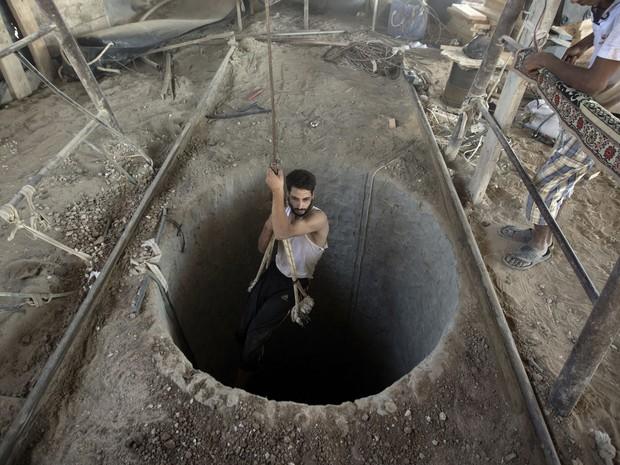 Um homem palestino entra em um túnel de contrabando sob a fronteira Gaza-Egito, no sul da Faixa de Gaza. As forças de segurança egípcias intensificaram uma campanha de repressão aos túneis de contrabando entre o Egito e Gaza. (Foto: Mahmud Hams/AFP)