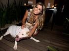 Com os cabelos longos e loiros, Babi Rossi posa com cachorro em evento