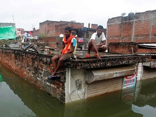 Homens em teto de local atingido por inundações em Allahabad, na Índia (Foto: Jitendra Prakash/Reuters)