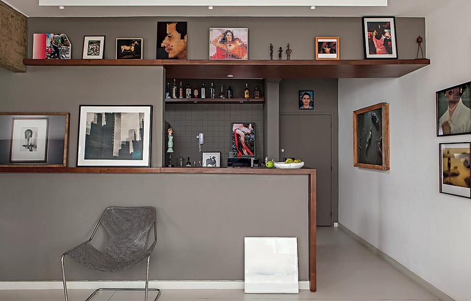 """A moldura de imbuia cobre o balcão, entre a sala e a cozinha, e segue como prateleira pelas paredes. """"Como o morador tem muitos quadros, pode apoiá-los nela e trocá-los à vontade"""", diz o arquiteto Gustavo Calazans. Dentro da cozinha, também há obras"""