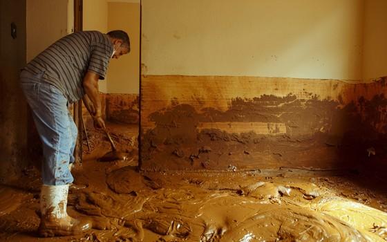 Morador  de Barra Longa tenta limpar a sujeira dentro de sua casa, dois dias depois do rompimento de duas barragens de rejeitos de mineração, de Fundão e de Santarém, ocorrido na tarde da quinta-feira (Foto: Daniel Marenco / Ag. O Globo)