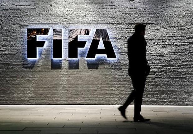 Jornalista caminha diante do logotipo da FIFA na sede da instituição na Suíça (Foto: Arnd Wiegmann/REUTERS)