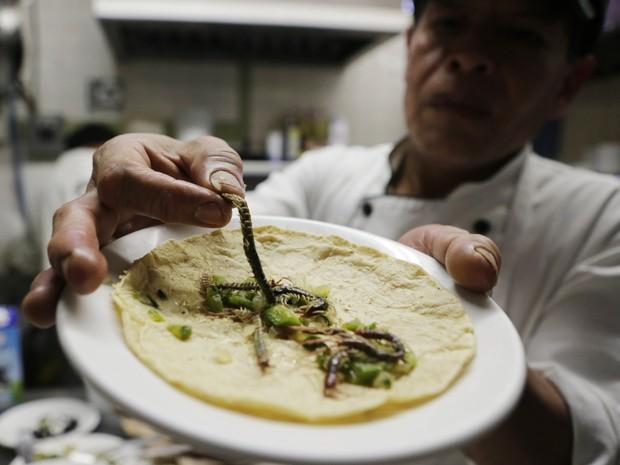 O chef de cozinha Ernesto Martinez mostra um taco sendo preparado com centopeias no restaurante La Cocinita de San Juan (Foto: REUTERS/Henry Romero)