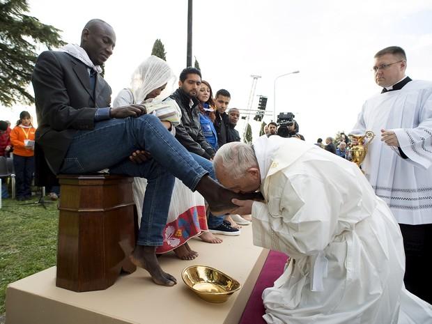 O Papa Francisco beija os pés de refugiados na Basílica de São Pedro – dentre eles, de três homens muçulmanos – durante tradicional ritual que precede a Páscoa (Foto: Osservatore Romano/Handout via Reuters )