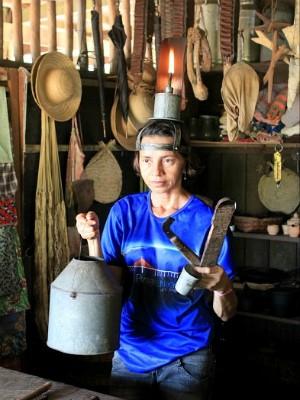 Guia mostra as ferramentas de trabalho dos seringueiros, na cabeça carrega uma poronga (Foto: Tiago Melo/G1 AM)