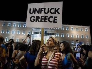 5/7 - Mulher segura placa com frase em inglês equivalente a algo como 'Desf*dam a Grécia', celebrando em manifestação em frente ao Parlamento grego em Atenas, após pesquisa mostrar que o resultado do referendo seria contra a proposta dos credores do país (Foto: Iakovos Hatzistavrou/AFP)