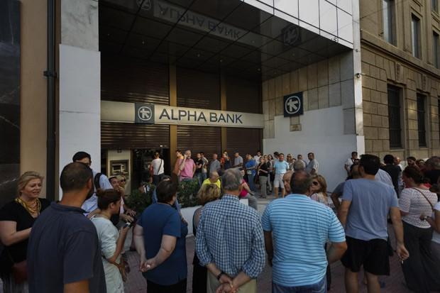 Gregos enfrentam fila para tirar dinheiro em um caixa eletrônico no centro de Atenas neste domingo (Foto:  AP Photo/Daniel Ochoa de Olza)